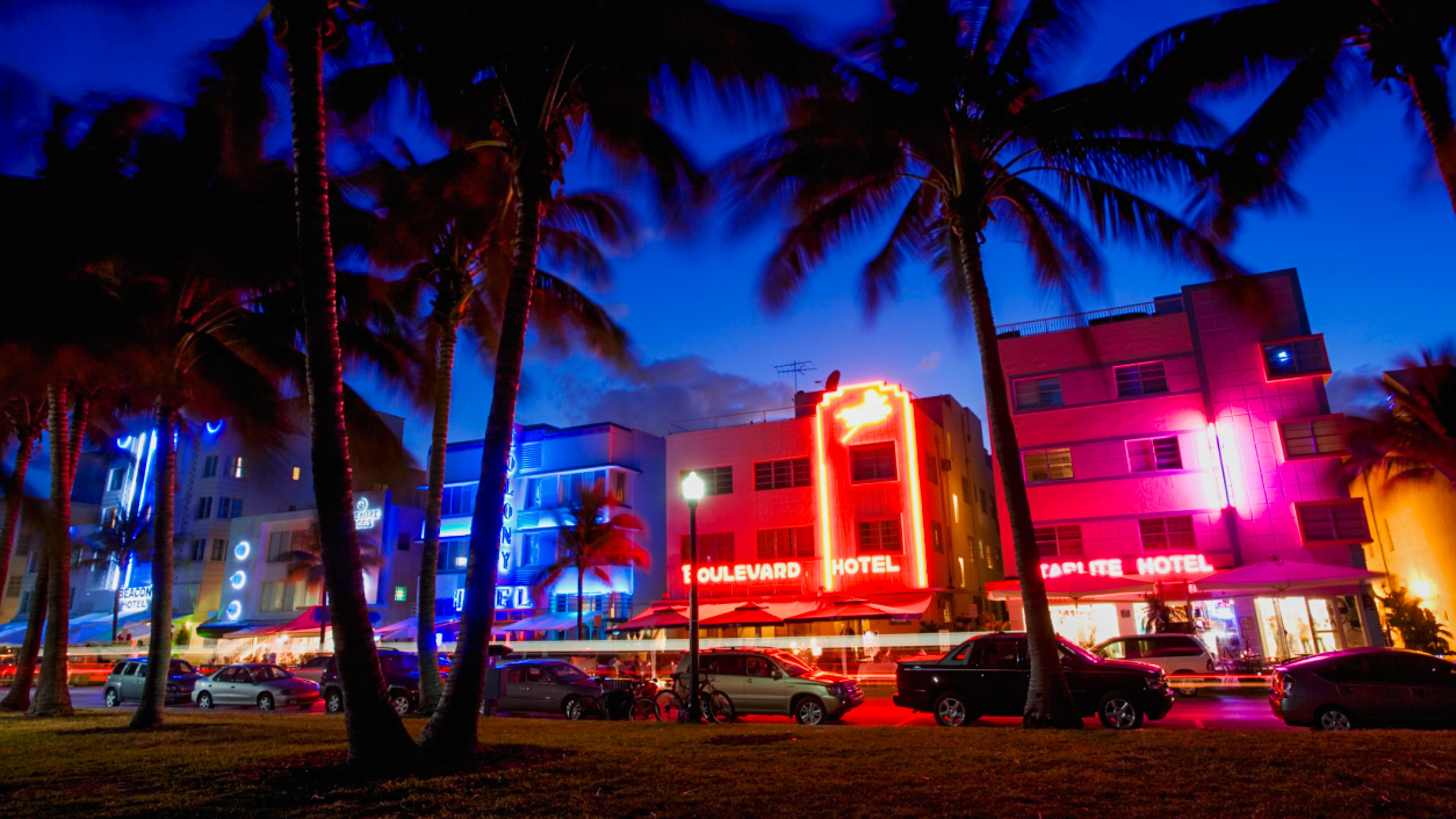 Modernos edificios a lo largo de una avenida con letreros iluminados con neón y palmeras