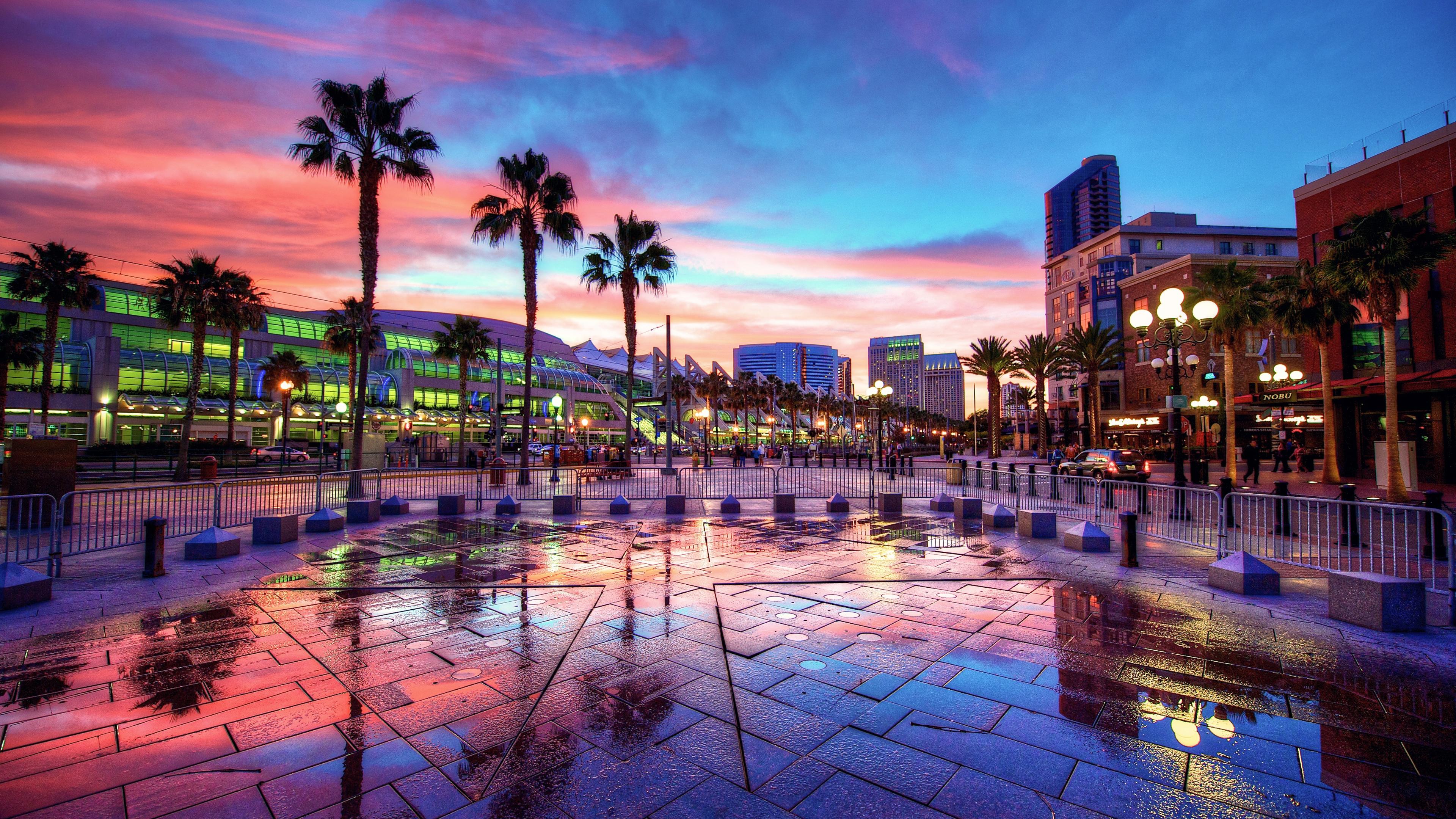 Palmeiras e áreas de estacionamento à frente de uma moderna área de compras ao pôr do sol