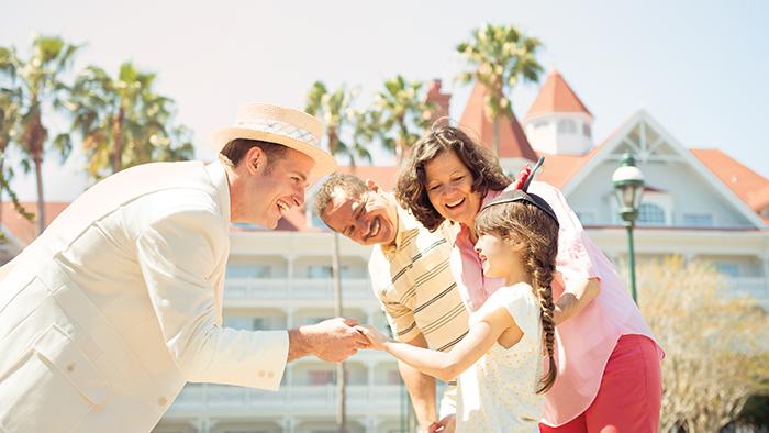 Un sonriente Miembro del Elenco del Disney's Grand Floridian Resort and Spa con traje victoriano saluda a una niña mientras sus padres observan
