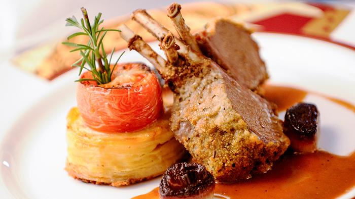 Costeleta de cordeiro com crosta de orégano e parmesão, tortinha de batata, tomate e chalota e um molho suave