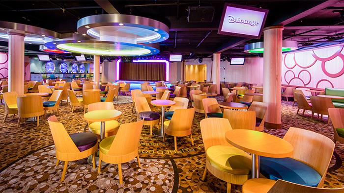 Salão repleto de cadeiras e mesinhas redondas com um grande lustre com formato de Mickey escondido acima
