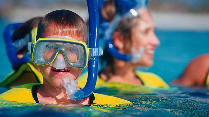 En el océano, un niño usa visor con snorkel mientras su mamá lo vigila