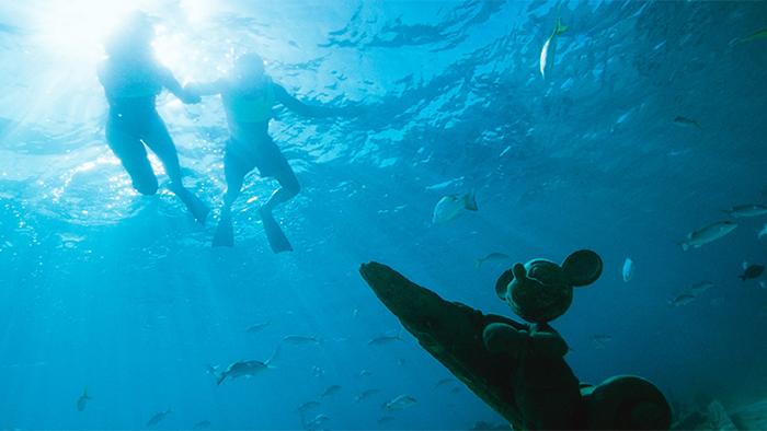 Dos visitantes de Disney Cruise Line practican snorkel sobre una estatua hundida de Mickey Mouse