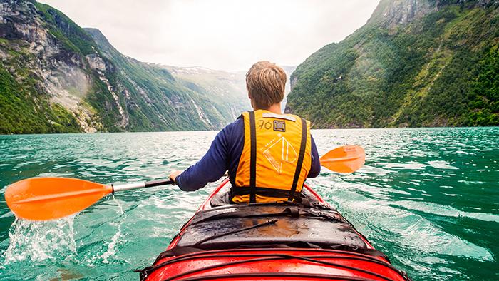 Um homem em uma canoa usa um remo para navegar por penhascos rochosos