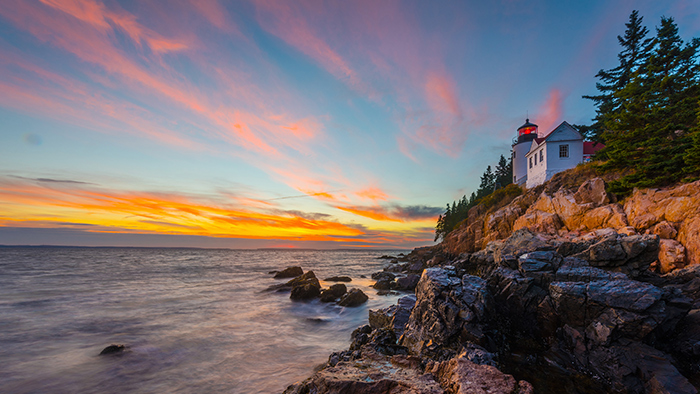 Un faro sobre un acantilado observa el mar durante el crepúsculo