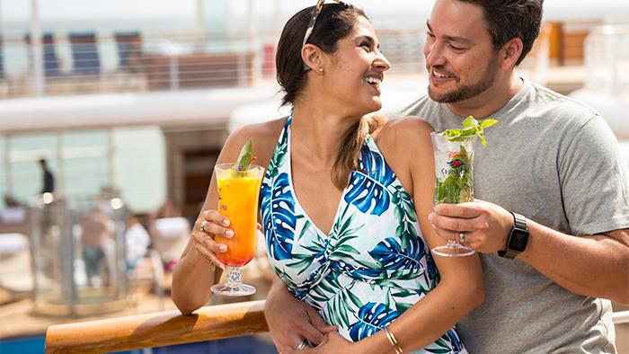 Una pareja disfruta unos cócteles tropicales en cubierta