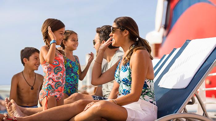 No deck, mãe e filha estão prestes a fazer um cumprimento com a palma da mão, enquanto o pai conversa com duas crianças