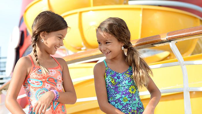 Duas meninas sorridentes na frente de um toboágua sinuoso