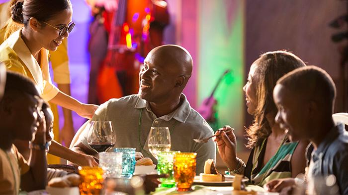 Uma família de quatro pessoas é cumprimentada por um tripulante da Disney Cruise Line durante o jantar