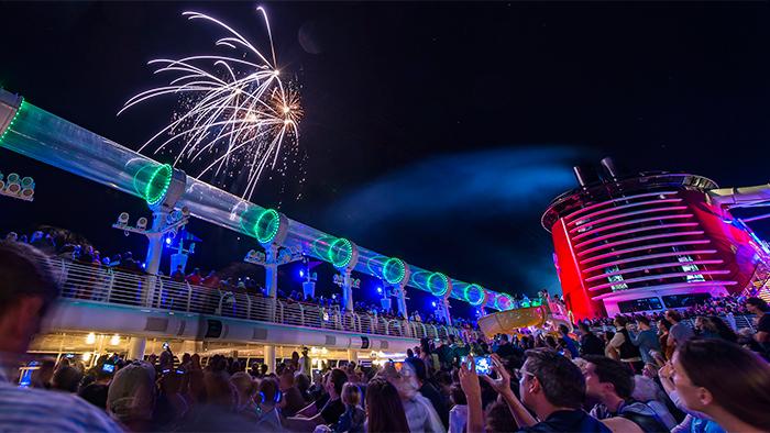 Fuegos artificiales estallan en el cielo nocturno sobre el barco de Disney mientras los visitantes los admiran asombrados
