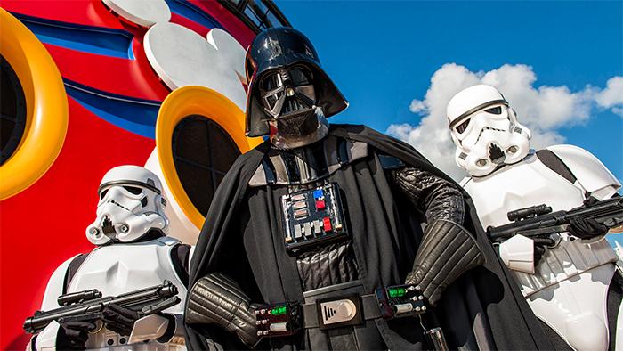 Darth Vader y 2 stormtroopers junto a una chimenea del barco de Disney Cruise Line, adornada con su logo